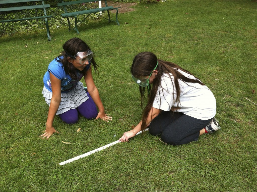 Macy and Olivia measure how far their rocket canister went.